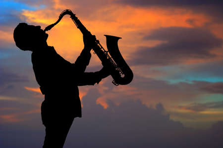 blues music: Saxophonist. Man playing on saxophone against the background of sunset