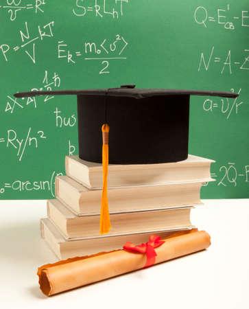 rewarded: Gortarboard y desplazamiento de la graduaci�n, en una pila de libro viejo maltrecho