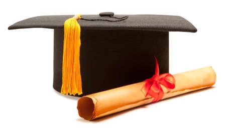 rewarded: Gortarboard y desplazamiento de la graduaci�n, aislado en blanco Foto de archivo