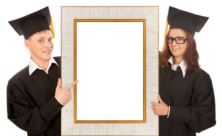 Two happy college graduate standing behind frame isolated on white background photo
