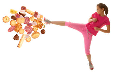 girl kick: Fit young woman fighting off bad food isolation on a white background Stock Photo