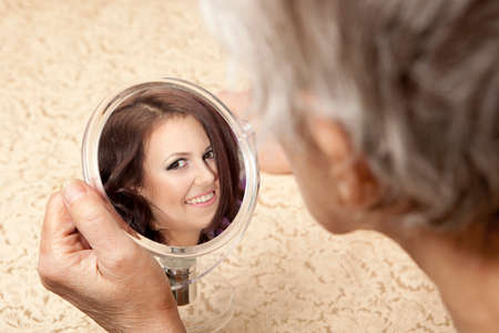 on mirrors: Old woman sees in the mirror youth
