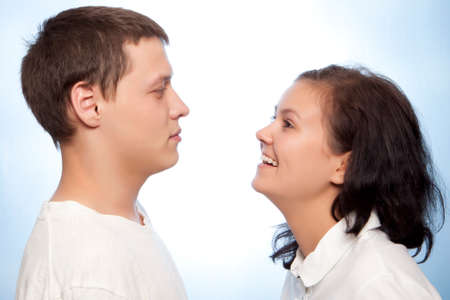 anecdote: Beautiful loving young couple smiling against a blue background