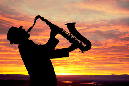saxofon: Saxofonista. Hombre que juega en el saxofón en el contexto de la puesta del sol