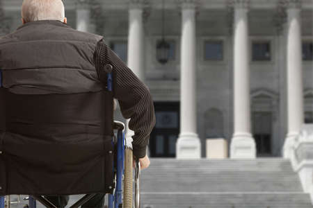 unaccessible: Wheelchair user in front of staircase barrier Stock Photo