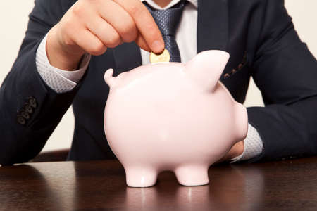 budget crisis: Businessman with pink piggy bank and coin