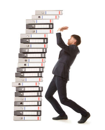office chaos: Frustrated businessman looking at pile of file folders
