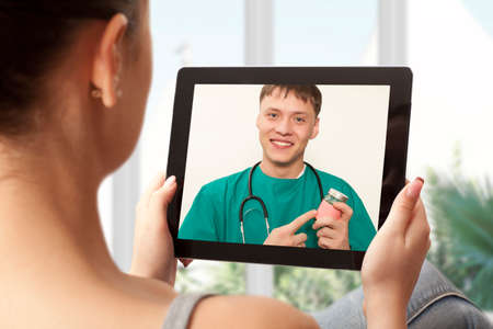 Woman having video chat with doctor on laptop at home Stock Photo
