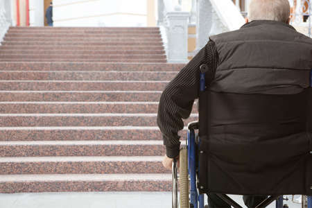Wheelchair user in front of staircase barrier Stock Photo
