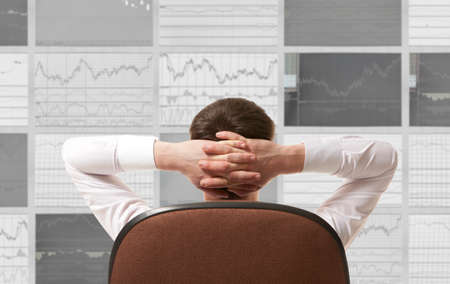 stock: Stock trader looking at monitors Stock Photo