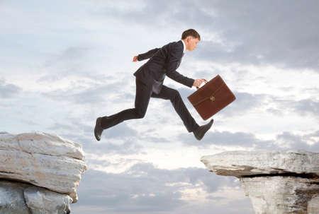 Jonge zakenman springen over rotsen met gap-concept