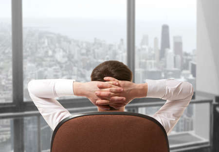 window view: Businessman sitting in office and looking in city