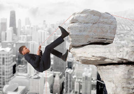 Young businessman scaling a rock   Business concept Stock Photo
