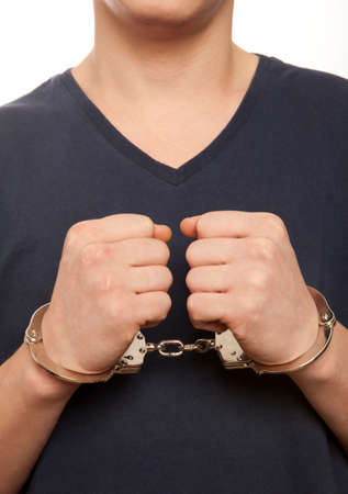 handcuffed hands: Close-up. Arrested man handcuffed hands at the back Stock Photo