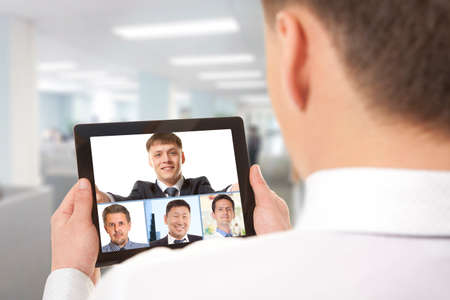 web conference: Cropped image of team businessman attending video conference with colleague on digital tablet