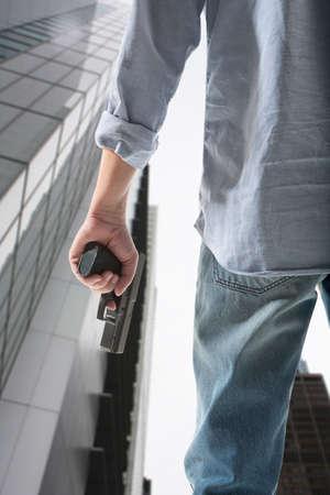 man holding gun: Man holding gun against an skyscraper background