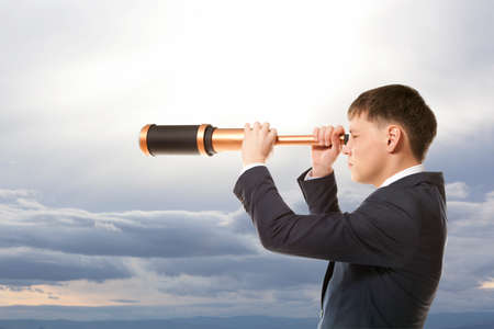 Business concept. Businessman looks through a telescope