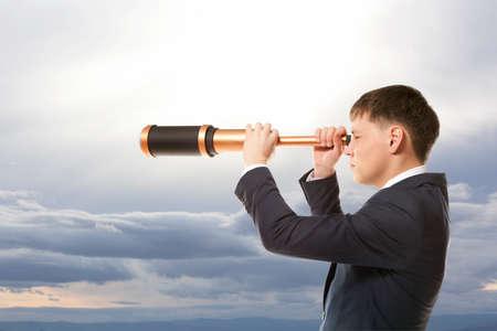 Concepto de negocio. El hombre de negocios mira a través de un telescopio