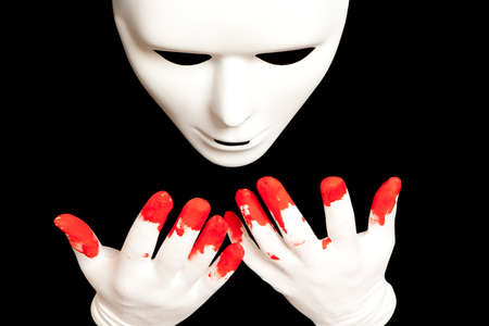 White theatrical mask and blood on their hands photo