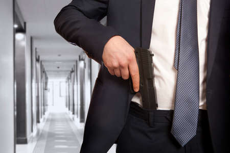 hand guard: Businessman in a suit holding a gun Stock Photo