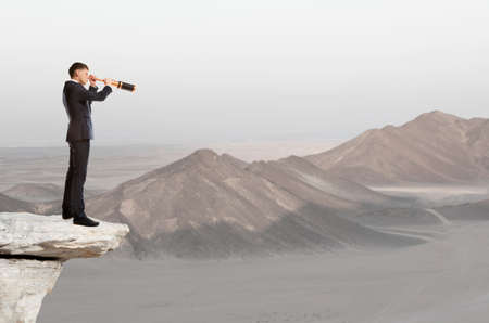 Businessman looks through a telescope. Concept for business photo