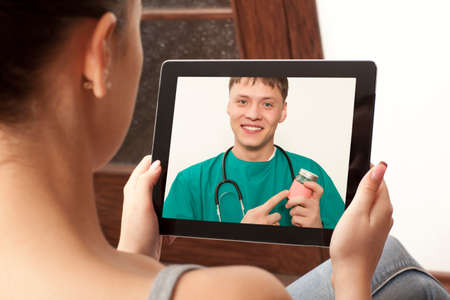 Woman having video chat with doctor on laptop at home photo
