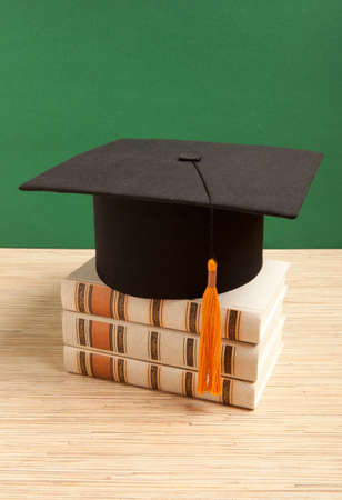 yellow tassel: Graduation hat with old book on the background of school board Stock Photo