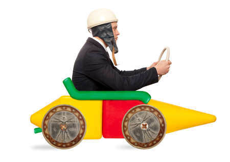 Young businessman driving fast on a toy car photo