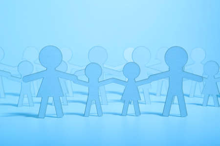 adopting: Paper family on blue background. Blue Light Stock Photo