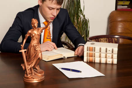 legality: Lawyer reading a book in the office