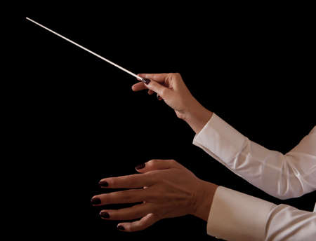 conducting: Orchestra conductor hands baton. Music female director holding stick Stock Photo
