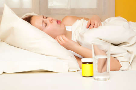 sleeping tablets: Cough. Female in bed at home caught cold, feeling bad, taking medicines Stock Photo