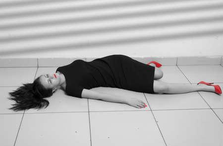 Crime scene imitation. Lifeless business woman lying on the floor photo