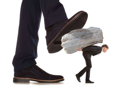 trample: Cared small businessman under big leg his boss, isolated on white background Stock Photo