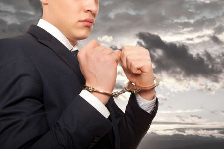 manacles: Worried caucasian middle aged businessman in handcuffs