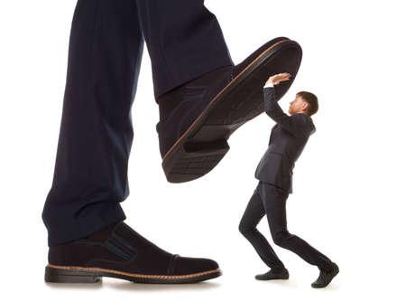 Soigné petit entrepreneur sous chapiteau jambe son patron, isolé sur fond blanc Banque d'images