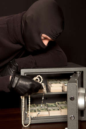 breaking the code: Thief burglar stealing dollar money during home safe code breaking Stock Photo