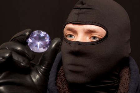looting: Thief. Man in black mask with a big diamond.Focus on thief
