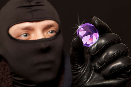 looting: Thief. Man in black mask with a big diamond.Focus on diamond