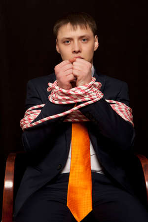 business problems: Businessman with hands tied in ropes. Business problems and difficulties