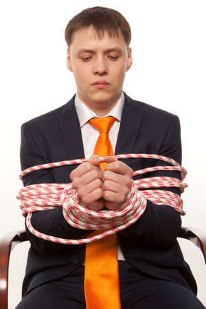 tied in: Businessman with hands tied in ropes. Business problems and difficulties