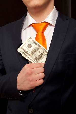 bribing: Businessman putting money in suit jacket pocket, concept for corruption, bribing
