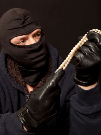 looting: Thief. Man in black mask with a pearl necklace. Focus on thief