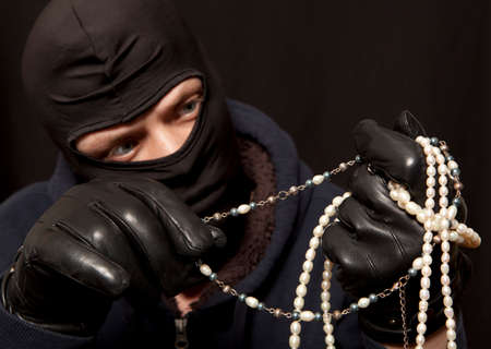 felon: Thief. Man in black mask with a pearl necklace. Focus on pearl necklace Stock Photo