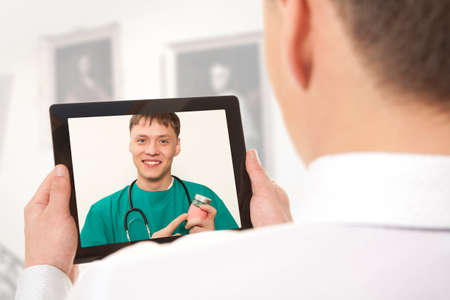Man having video chat with doctor on laptop at home photo