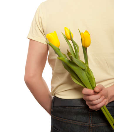 gift behind back: Man hiding bouquet of flowers tulip behind his back isolated on white background Stock Photo
