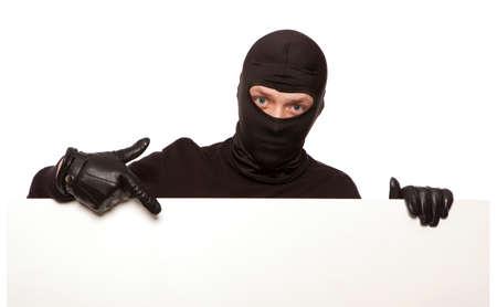Ninja. Robber versteckt sich hinter einem leeren weißen Schild mit Platz für Text. Isoliert auf weißem Hintergrund