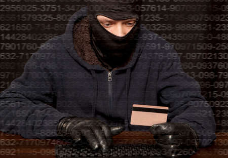 cyber crime: Hacker in a balaclava with laptop