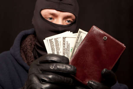 crook: A thief sealing from a brown leather purse Stock Photo