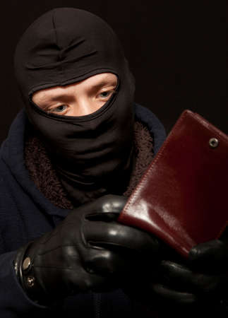 pickpocket: A thief sealing from a brown leather purse Stock Photo